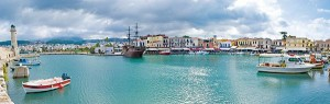 RETHYMNO, GREECE - OCTOBER 10, 2013 - The panorama of Old Venetian Port with fishing boats, medieval warship, lighthouse and old cafes and restaurants, on October 10 in Rethymno.